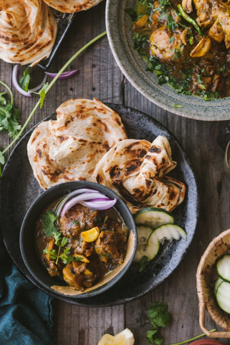 Flat lay view of Garlic Chicken Curry with paratha and salad
