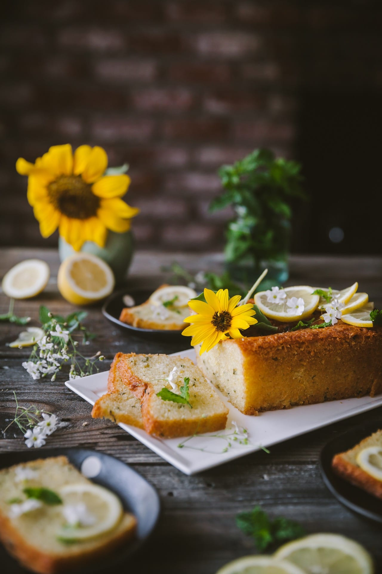Lemon Mint Cake styled with flowers and fresh lemon and mint. It's sliced and the slices are kept next to the rest of the cake loaf