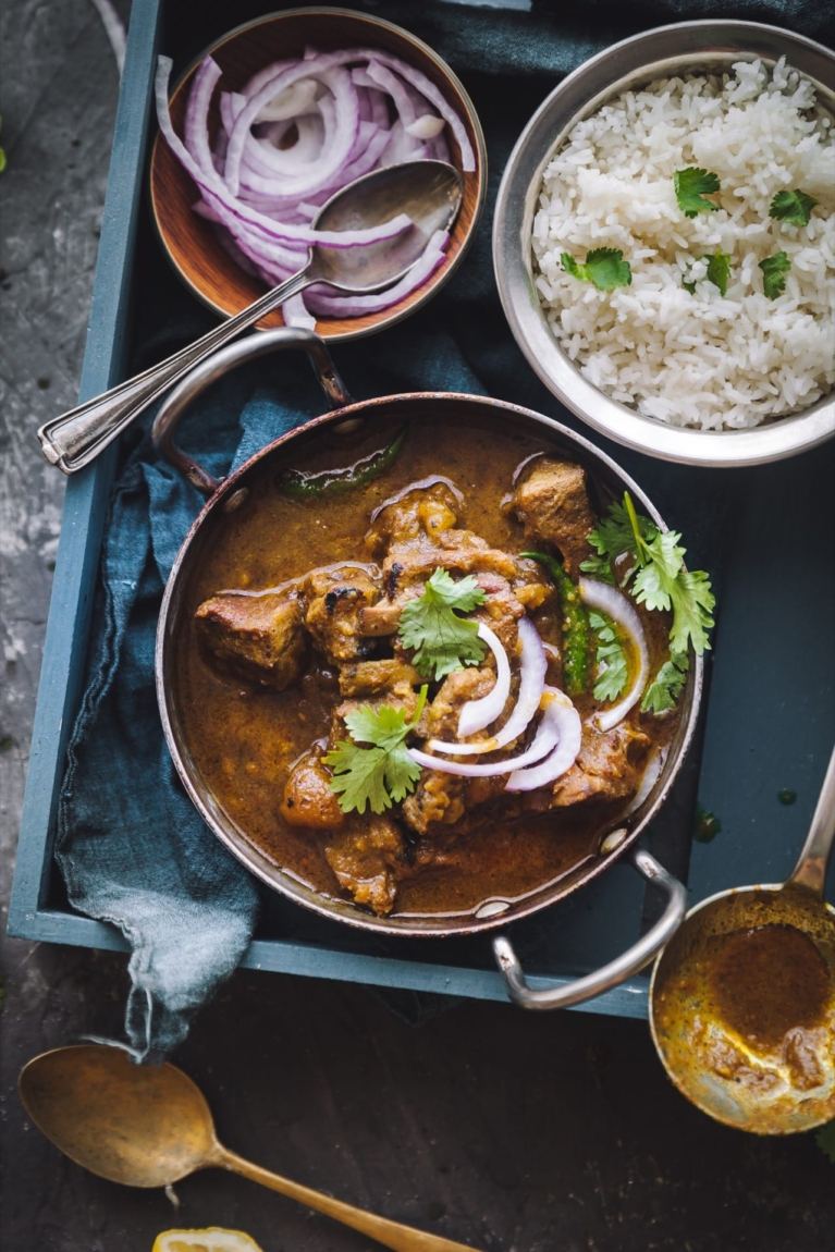 Over the top view of Sunday Mutton Curry in a bowl served with rice in a different bowl.