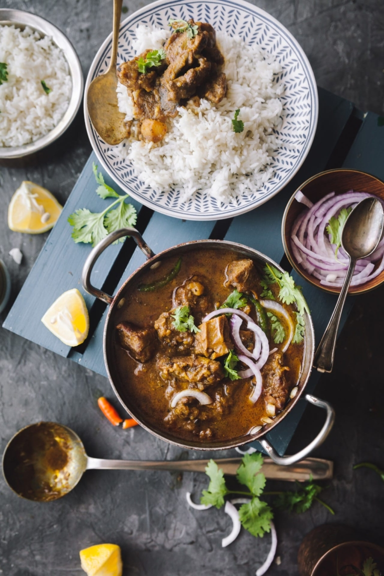 Over the top view of Sunday Mutton Curry along with a plate with rice and curry on the side. Sliced onion in a bowl and rice in a bigger bowl.