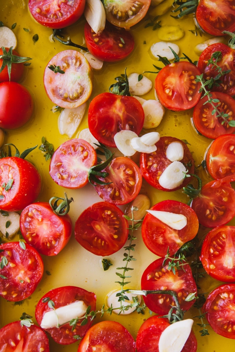 Tomato sliced in half with garlic, herbs and oil ready to be baked