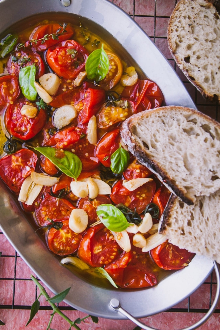 close up view of Tomato galic and basil on a tray with oil topped with two slices of bread and few bread slices are kept on the side