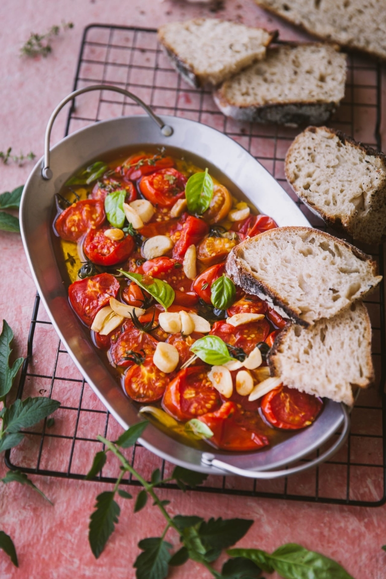Tomato galic and basil on a tray with oil topped with two slices of bread and few bread slices are kept on the side