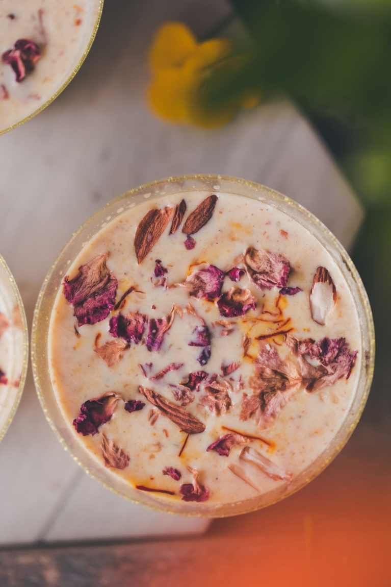 Close up photo of milk based Indian drink, garnished with rose petals and chopped nuts.